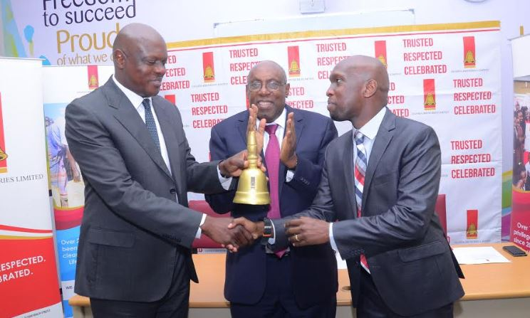 Uganda Breweries Out going Managing Director Mark Ocitti (L) hands over The Bell to the new UBL Managing Director Alvin Mbugua (R). Looking on is Japeth Katto the UBL Board Chairman.