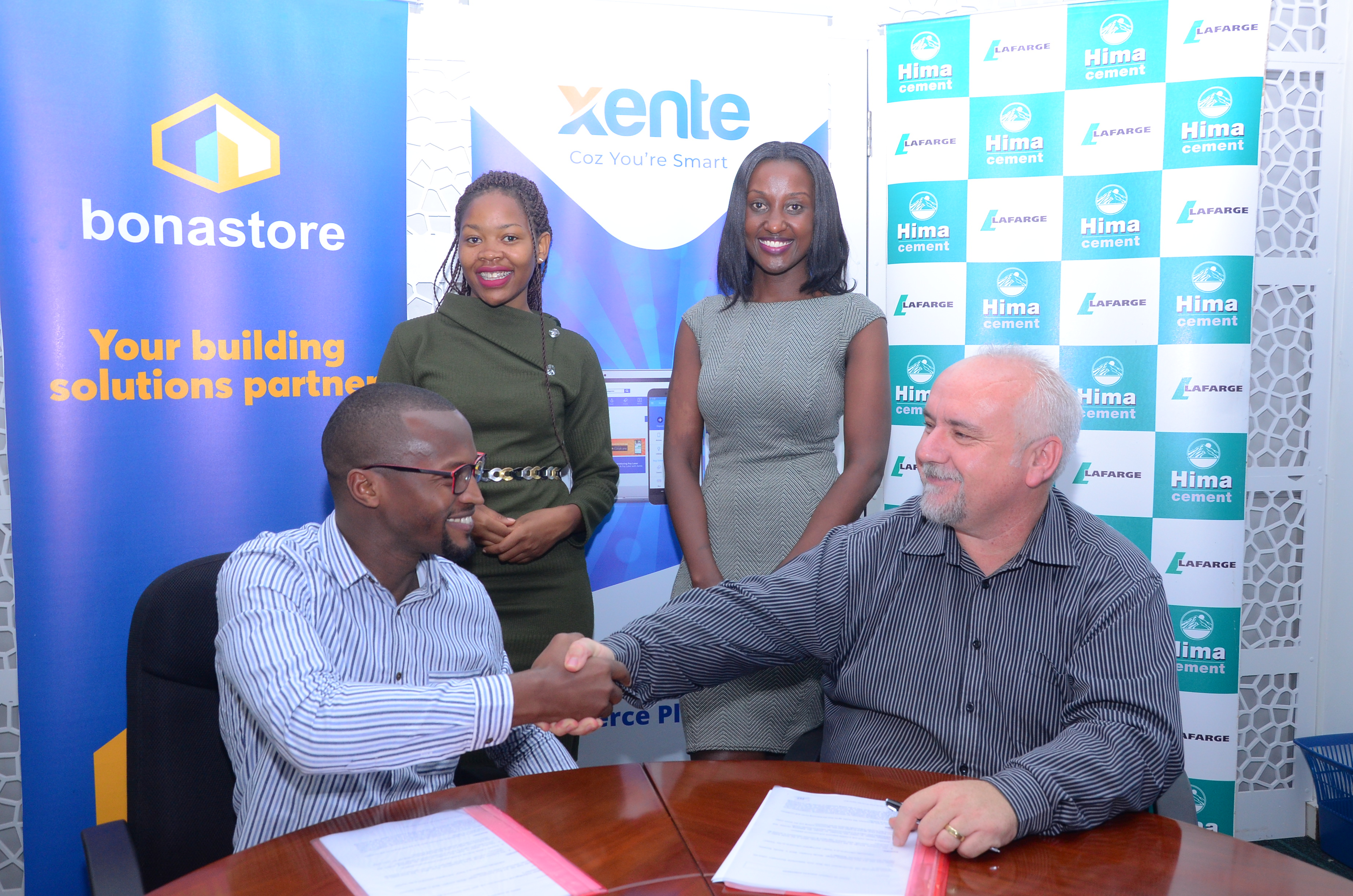 Francis Nkurunungi, Xente's Chief Operations Officer (Seated L) and Paul Bernard Kelly (Seated R), Hima Cement's Retail Manager sign an MoU to open an online shopping platform.