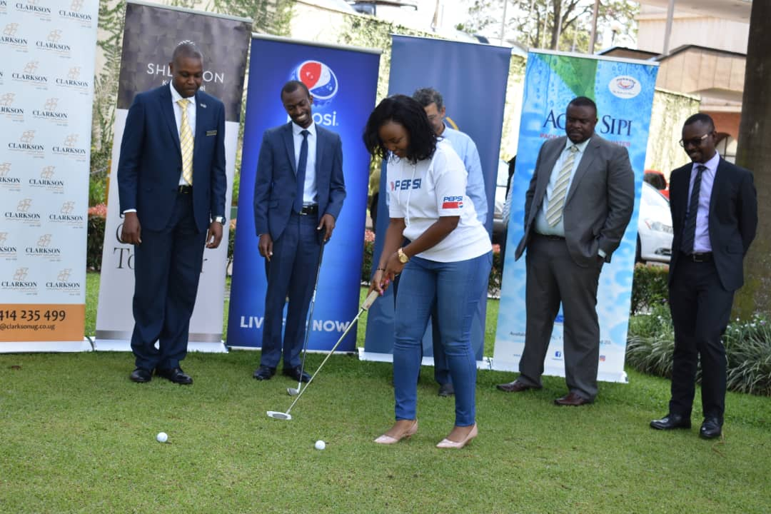 Mrs. Tracy Kakuru Otatina (C)  Corporate Communications Manager Crown Beverages Limited(CBL) putts as  Mr. David Sekitoleko (L) Business Development Consultant Sheraton Hotel Kampala, Mr. Allan Muhinda (2nd L), Head Global Market Sales at Stanbic Bank, Mr.Daniel Kairu (2nd R) Head of Business Development at ICEA, and look on.