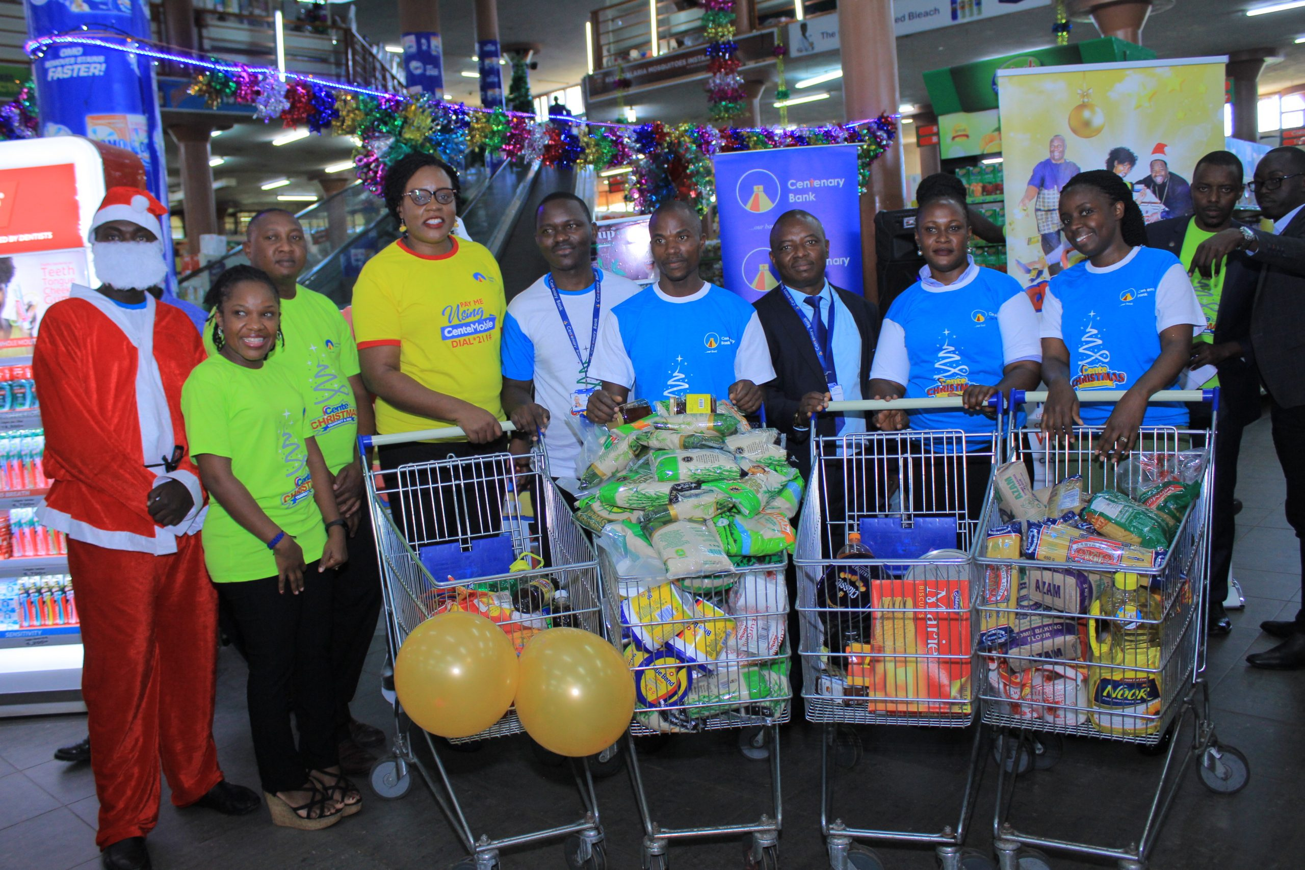 Mrs. Beatrice Lugalambi (4th L), General Manager Corporate Communications , and Marketing at Centenary Bank, poses for a photo with CenteChrismas Trolley Dash Shopping Bonanza winners, and Centenary Bank Staff. This was during the reward of the 1st batch of Kampala Trolley Dash winners.