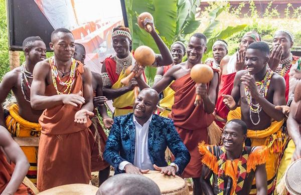 State Minister for Tourism, Hon. Godfrey Kiwanda joins the Ndere Cultural troupe during their performance at the Tulambule Christmas campaign launch.