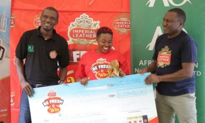 Mr. Manzi Ivan Head of Sales, Marketing and Customer Service at African Queen (L), Mr. Amos Oula, the country Manager PZ Cussons (R) hand over a dummy cheque to Ms. Doreen Nabakooza.