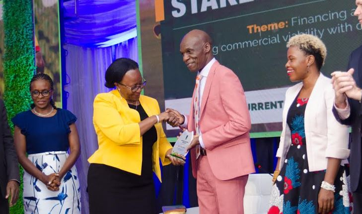 Mrs. Sarah Walusimbi, the Chairperson Board of Directors at Agriculture Business Initiative Development (aBi) handing over a plaque of appreciation to Mr. Collins Apouyo, the Chief of Party at Development Alternatives Incorporation (DAI) and a panelist at the aBi Development Annual Stake Holders Forum and 10 Years Celebration.