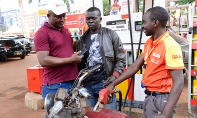Ronald Ngobi, the station manager of Shell Bugolobi rewarding a boda rider who won fuel during the campaign.
