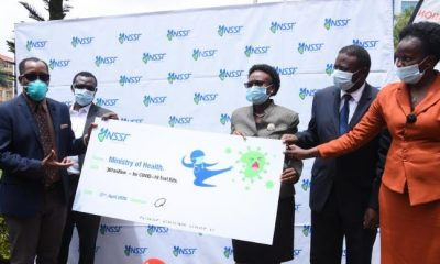 L-R: NSSF Managing Director Richard Byarugaba and deputy MD Patrick Ayota hand over a dummy cheque to Dr, Ruth Aceng the Minister of health, Prof. Ponsiano Kaleebu MD Uganda Virus research institute and Susan Nabadda, ED Uganda National Health Laboratory Services