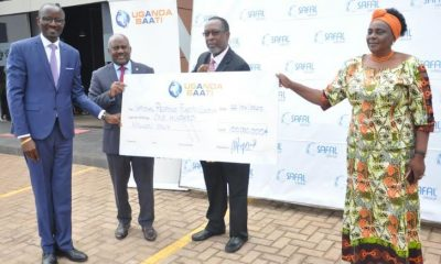 Hon. Mary Okurut (R) receives a shs100million dummy cheque on behalf of the government from Chief Executive Officer at Uganda Baati George Arodi (Left) and Uganda Baati Board Chairman Alan Shonubi (2nd right) as Chairperson National COVID-19 Force Katongole looks on.