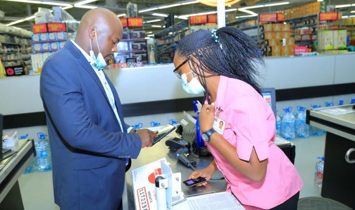 A customer pays at the till using Airtel Money Pay assisted by a Game Store Executive.
