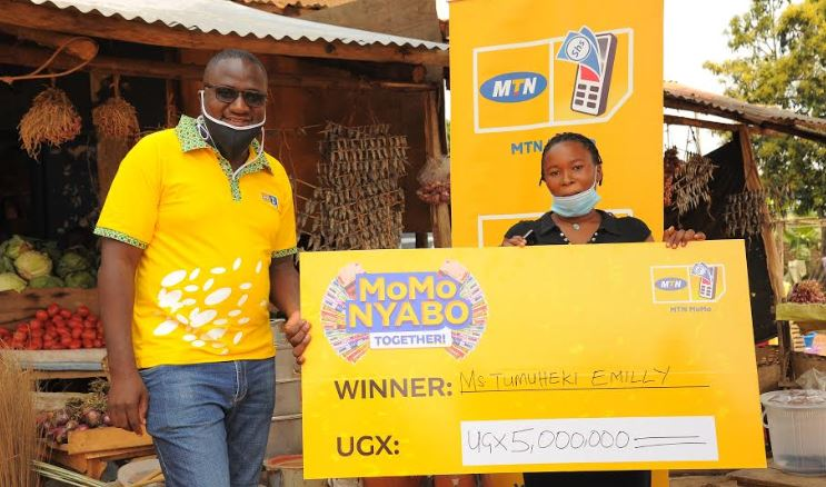 MTN's Jimmy Ssempuuma (L) hands over Emily Tumuheki's cheque.