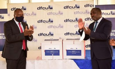 dfcu Bank's CEO, Mathias Katamba handing over refurbished desktop computers to State Minister for Defence and Veteran Affairs Christopher Kibanzanga