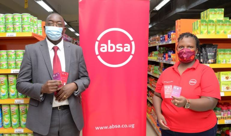 ichael Segwaya, Absa CFO and ED and Ann Kiconco, acting Retail Banking Director pose with the contactless-enabled Vertical Debit Cards during the launch recently.