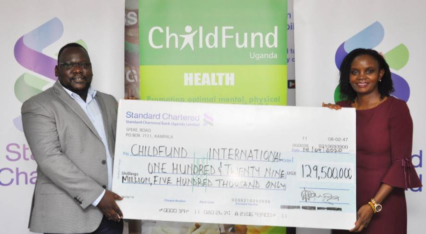 ChildFund Uganda Country Director Moses Otai receives dummy cheque from Regina Mweru Mukiri, the Head of Corporate Affairs Standard Chatered Bank Uganda.