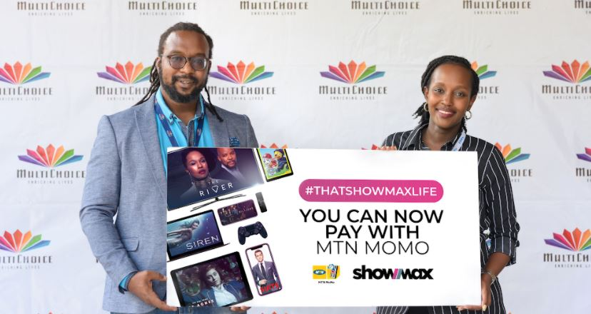 Colin Asiimwe (L) Head of Marketing at MultiChoice Uganda and Joa Kizza Semanda (R) the Public Relations and Communications Manager at MultiChoice Uganda, displaying a Showmax - MTN Mobile Money payment option placard.