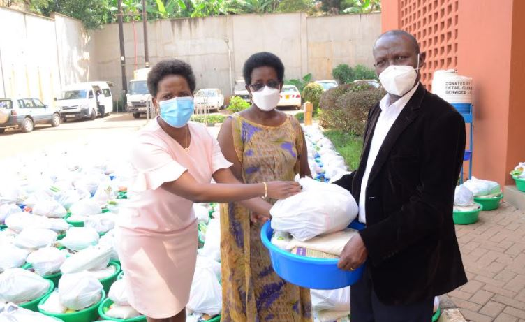 Ms Anne Juuko, CEO of Stanbic Bank Uganda and Dr. Diana Atwine, the Permanent Secretary Ministry of Health, hand over the essential items to Dr. Nehemiah Katusiime, Executive Director of Kawempe Hospital.
