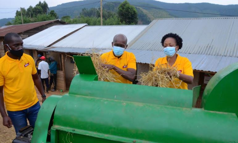 Alvin Mbugua, UBL MD and Juliana Kagwa, UBL Corporate Relations Director test a modern threshing machine donated by the brewery to barley farmers.
