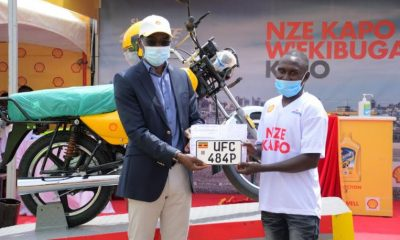 Mr. Gilbert Assi, Managing Director of Vivo Energy Uganda hands over a motorcycle to one of the lucky winners during the final handover ceremony held at Shell Banda on Friday.