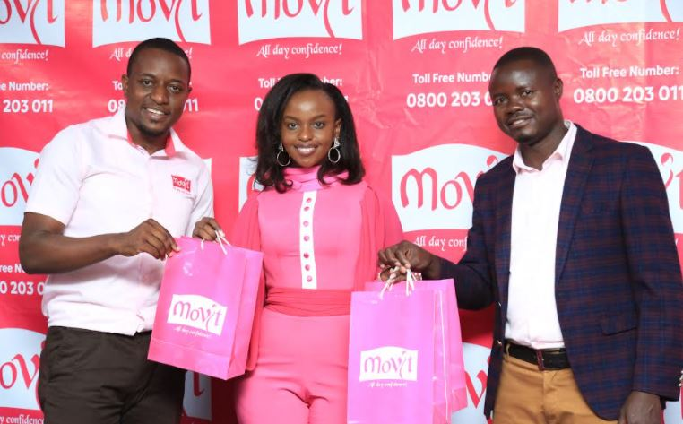 Robert Kitenda (L), Head Marketing Movit Products Limited, and Stephen Adinyai, Movit Brand Manager pose with Gloria Mulugi Senyonjo aka Baby Gloria (C) after being unveiled as the Movit Brand Ambassador at Movit Head Offices.