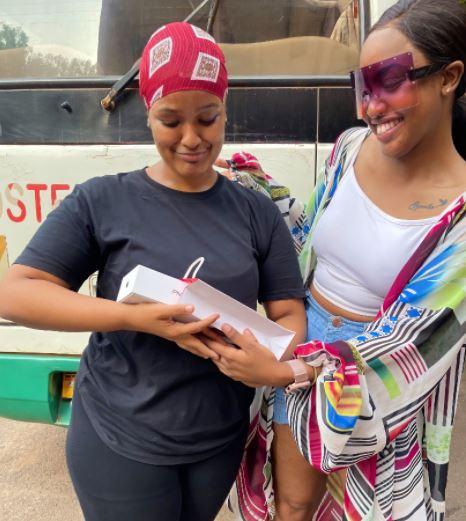 Lynda Ddane hands over the brand new iPhone X to Ms Nabukenya.