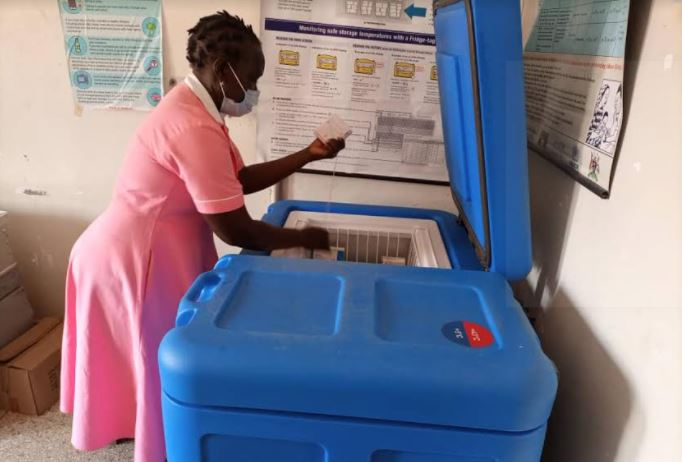 A nurse at bidibidi health centre iii checks for a vaccine in the solar vaccine fridge donated to the health centre by MTN