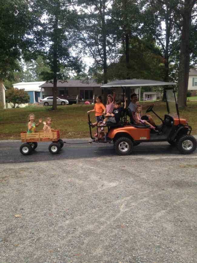 A slew of grandkids on a golf cart