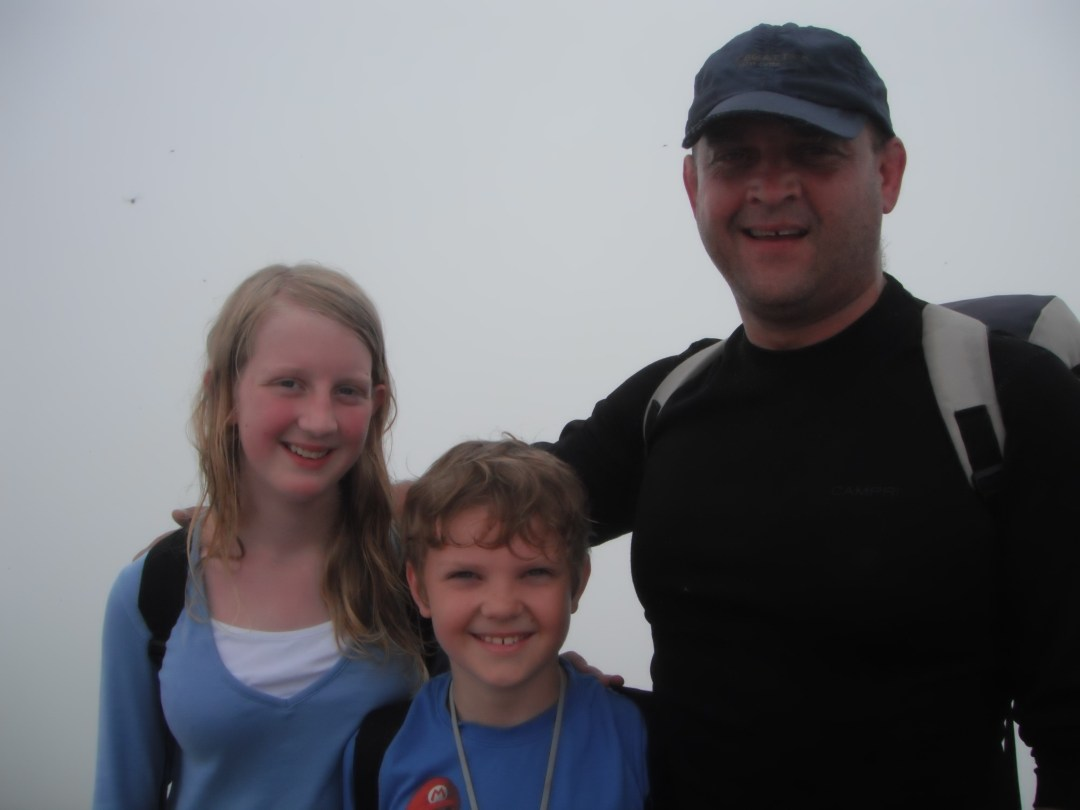 Asa, Xene and Lochlan at the summit of Mount Snowdon in cloud