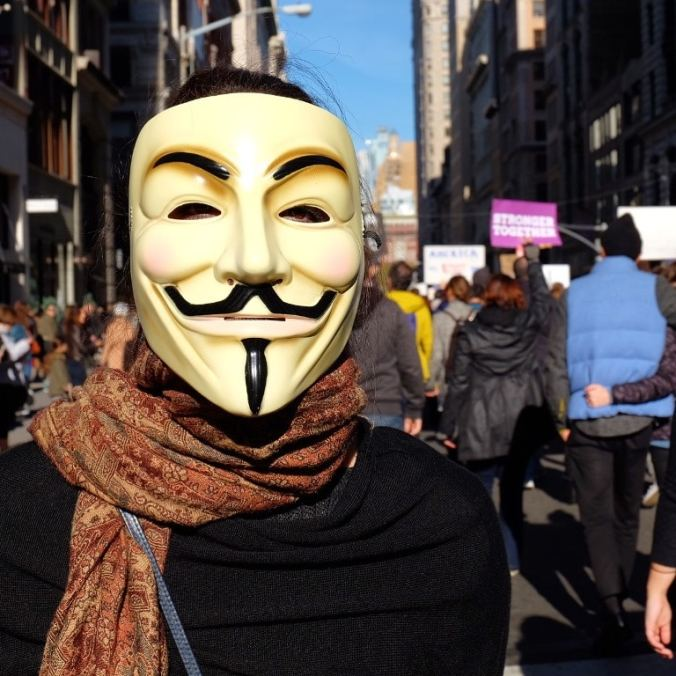 A protester wearing their Guy Fawkes mask
