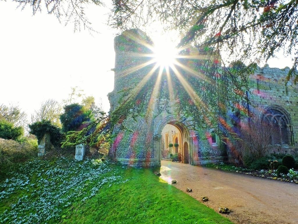 Benington Lordship Gardens keep with a starburst sun behind it