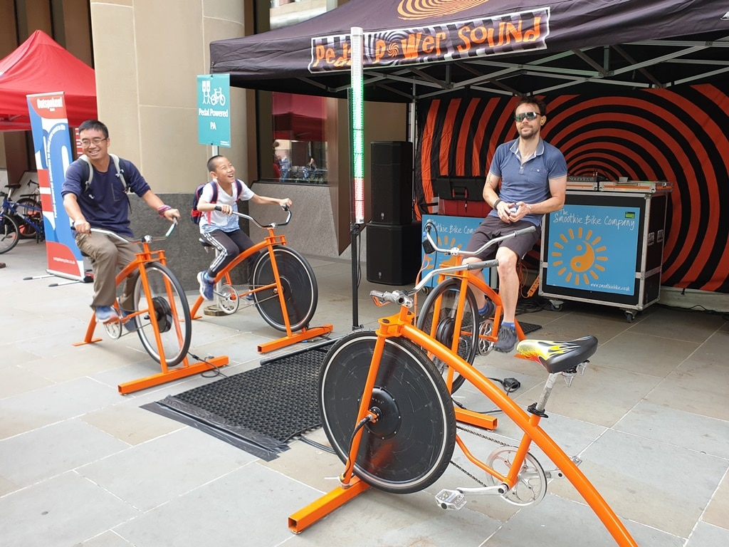 Three cyclists pedalling stationary bikes at Ride London