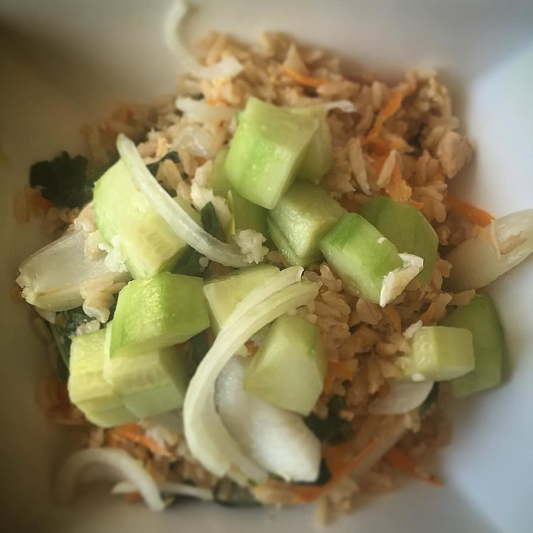 On the menu tonight: spicy chicken and veggie fried rice topped with a fresh cucumber and onion salad.