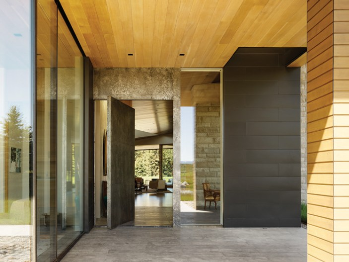 The covered porch at the home's entry is matched in artistry with a custom pivot door that features acid-etched steel.