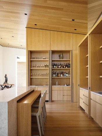 Custom millwork adds warmth to the kitchen and bar area.
