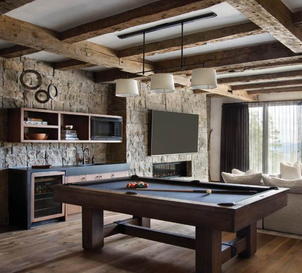 A pool table, mini kitchen, and plush sofa from Restoration Hardware's Cloud Modular Collection create an inviting place to gather, relax, and savor the mountain views in the family's recreation room.
