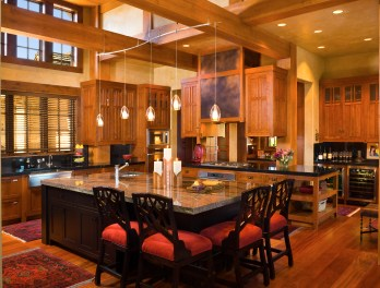 "The showcase kitchen functions comfortably with 50 guests or intimately with just two people. Brazilian granite on the island and ""Absolute Black"" granite on the countertops sleekly offset the custom cabinetry by Mountain High Woodworks of Bozeman."
