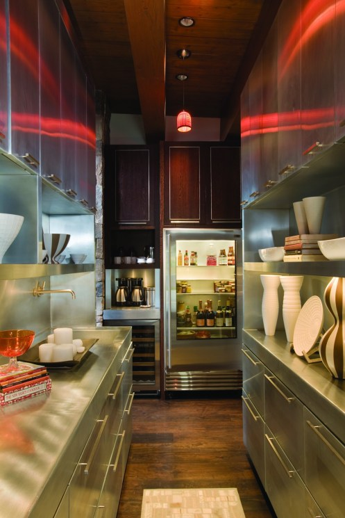 Clean lines of gleaming stainless cabinetry shelters practical accouterments for entertaining as well as a fine art ceramic collection including work by Elsa Rady, among others.