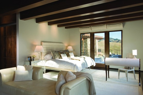 Contemporary lines in furnishings blend effortlessly with 100-year-old reclaimed beams in the master suite.