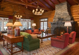 The handcarved timber trusses and original stacked stone fireplace anchor the main living area in historical detailing, while a color-scheme of jewel-toned red and green imply luxurious sophistication.