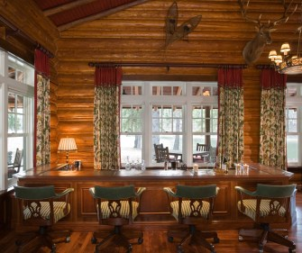 Tim Fox Construction took care to preserve original round, chinked logs, while interiors were respectfully updated by Warren Sheets Design's, using the contrast of crisply painted white double-hung windows in the living room that overlooks the Swan Ri