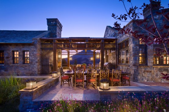 Architect Darin Hoekema, of Locati Architects cultivated an outdoor kitchen and entertaining area in this Yellowstone Club residence that functionally connects the main house with an outbuilding, provides shelter and ambience for outdoor dining and artfully frames the view of Lone Peak.