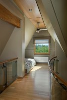 Utilizing what was once inaccessible attic space, architect Mitch Blake designed and built a steel and glass staircase to reach the top floor, converting into a lofty bedroom.