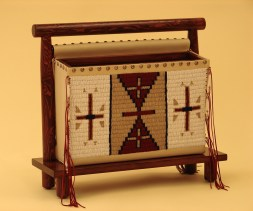 """Magazine Rack The beaded magazine rack made in the tradition of Thomas Molesworth is handmade and stitched one bead at a time from 45,000 beads, by artisan Susan Warner. 21""""H x 8""""D x 21.4""""W."""