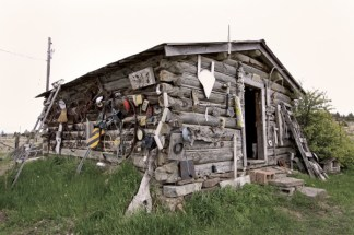 Jerry Iverson's studio, located north of Big Timber. The cabin was one of the original buildings on the land. The outside is adorned with various objects, including old telephones and a cassette boom box.