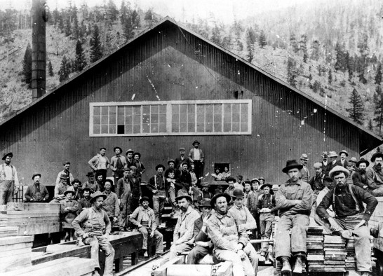 Dozens of workers sit or stand on lumber piles at the ACM Sawmill before 1908. Photo from University of Montana Maureen and Mike Mansfield Library