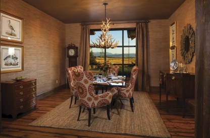 """The walls in the dining room are covered with grasscloth, a fine cloth made from woven plant fibers, for a high-end rustic appeal. And, as the open floor plan of the home allows visible access to the living room, """"no matter where you sit from the table, everybody has a view of the mountains from their chair,"""" said Jim Hodapp."""