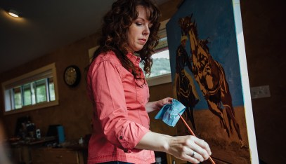 In her Gallatin Valley studio, Meagan Abra Blessing dabs paint from her pallette to the vibrant canvas in progress.