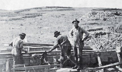 "Extracting sapphires at the English Mine was similar to placer gold recovery. In this photograph, miners clean a sluice box. The fence-like contraption behind the men, or ""metal riffles,"" has been removed from the bottom of the sluice boxes."