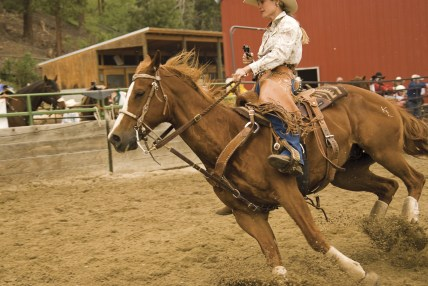 Dirt flies as national champion Kenda Lenseigne and her horse, Justin, pound through a turn.