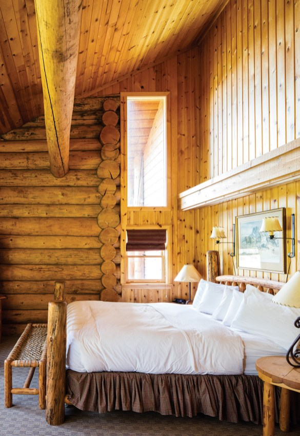 Daylight streams into a cozy log cabin guest room.