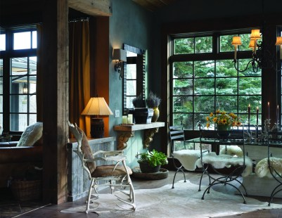 An elegant glass dining room table is augmented with sheepskin rugs that give the room a rustic and comfortable feel.