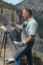 "Dwayne Harty painting en plein air overlooking the Nahanni River and Pulpit Rock, Nahanni National Park, Northwest Territories. ""In the three years traveling the Y2Y (Yellowstone to Yukon) mountain corridor I completed 110 plein air paintings as color reference preparatory to completing the larger easel paintings,"" Hardy said."