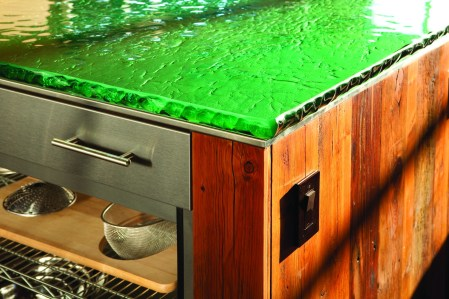 The green glass counter offers a touch of color to the industrial-style kitchen.