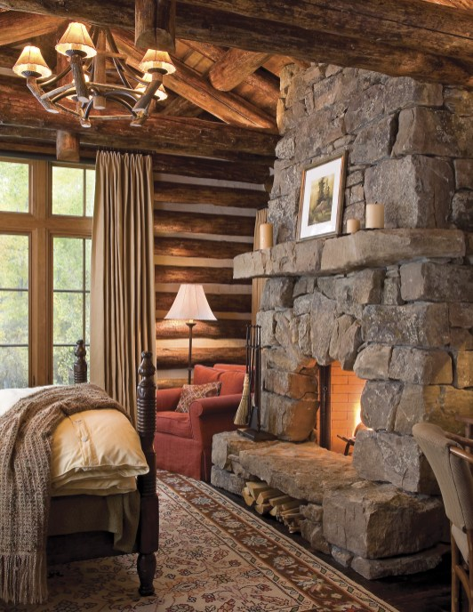 In the master bedroom, lush linens and a roaring fire epitomize the beauty of cabin life.
